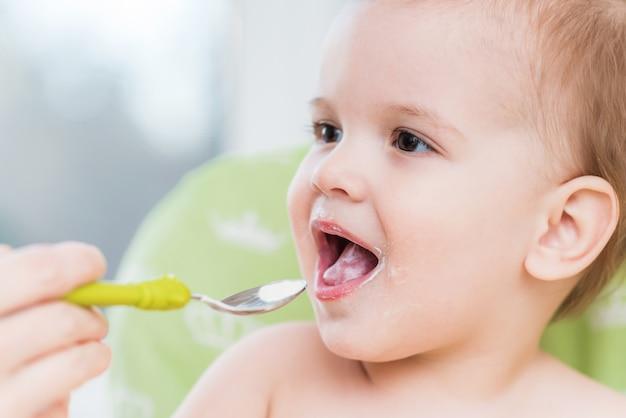 Mères nourrissant le bébé avec du fromage cottage