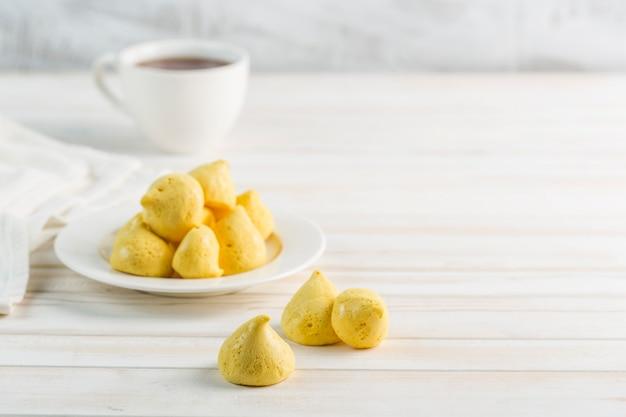 Meringue de banane dans une assiette blanche et une tasse de thé sur un fond clair. sans sucre