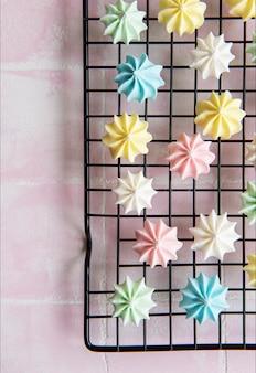 Meringue multicolore sur une grille de cuisson sur un fond de tuile rose