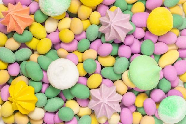 Meringues colorées et cacahuètes glacées isolés sur fond blanc. vue de dessus.