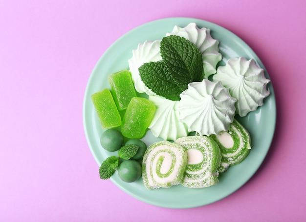 Meringues de couleur menthe, bonbons à la menthe et gâteau savoureux sur fond de couleur