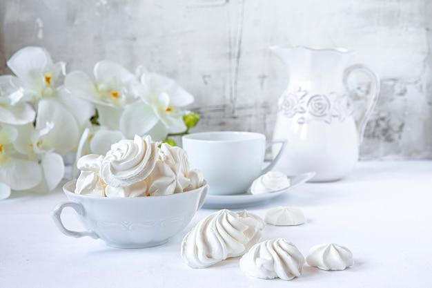Meringues. gâteau au sucre protéiné pour le thé ou le café. fond clair matin blanc. bonbons