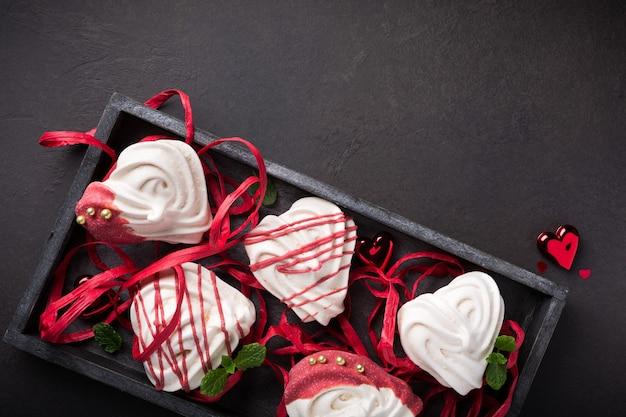 Meringues maison en forme de coeur dans une vieille boîte en bois pour la saint-valentin, vue du dessus, espace copie