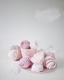 Meringues roses et blanches sur fond blanc. plume blanche volante