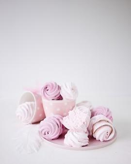 Meringues roses et blanches sur fond blanc.