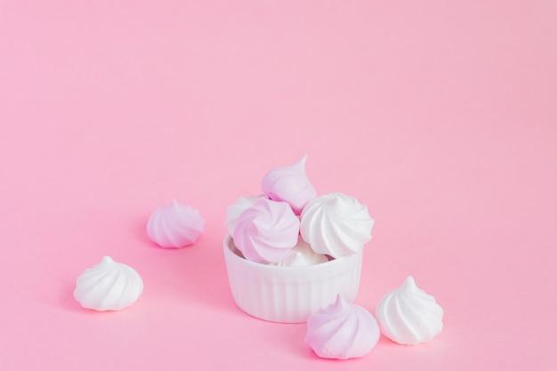 Meringues torsadées blanches et roses dans un bol en porcelaine sur fond rose, carte de voeux, espace copie