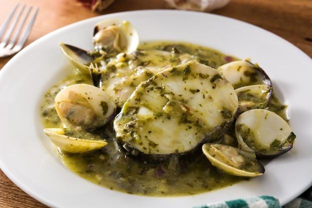 Merlu et palourdes avec sauce verte sur table en bois recette espagnole typique