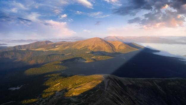 Merveilleuse aube dans les montagnes, les rayons du soleil illuminent les sommets des montagnes à travers le brouillard.