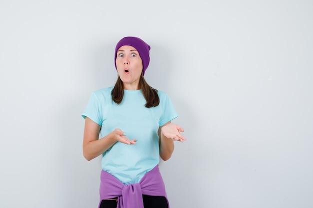 Merveilleuse dame faisant semblant de montrer quelque chose, ouvrant la bouche en chemisier, bonnet et ayant l'air terrifiée. vue de face.