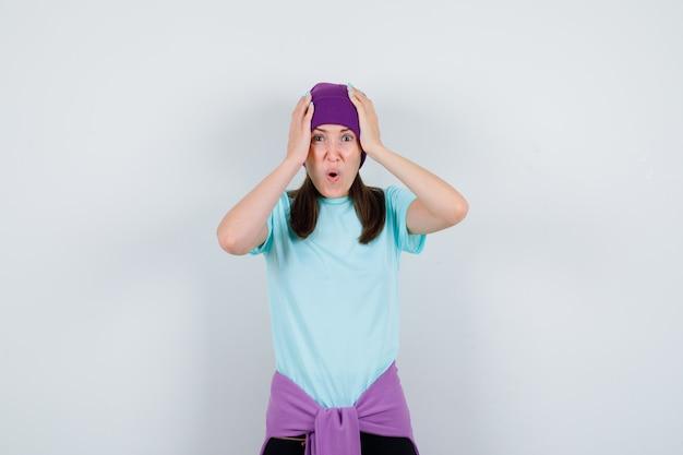 Merveilleuse dame avec les mains sur la tête, ouvrant la bouche en blouse, bonnet et l'air terrifiée, vue de face.