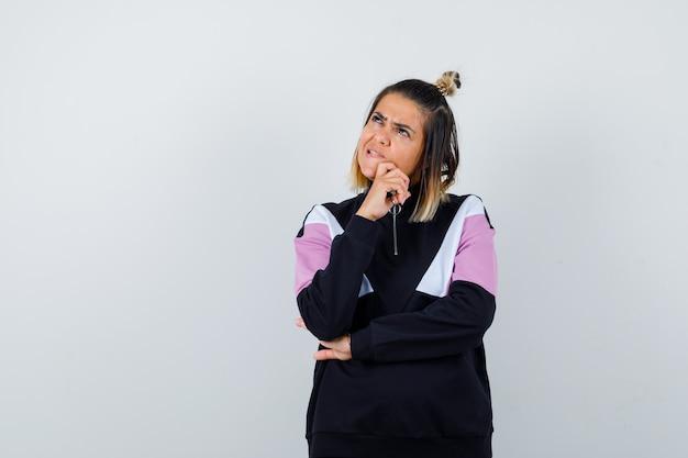 Merveilleuse Dame En Sweat-shirt Gardant La Main Sur Le Menton Et Semblant Réfléchie Photo gratuit