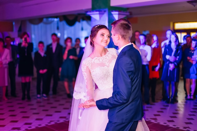 Merveilleuse danse de mariage de jeunes mariés heureux dans le hall du restaurant avec des invités