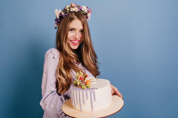 Merveilleuse femme aux cheveux longs posant avec un délicieux gâteau