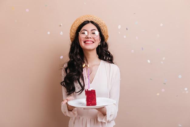 Merveilleuse femme japonaise aux cheveux bouclés tenant un gâteau. vue de face de la femme chinoise dans des verres pour célébrer l'anniversaire.