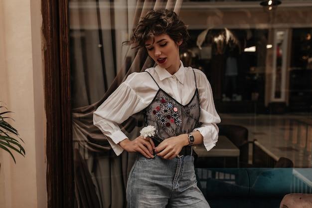 Merveilleuse femme en jeans et chemise avec dentelle noire et manches longues posant au café. femme aux cheveux courts tenant une fleur à l'intérieur.