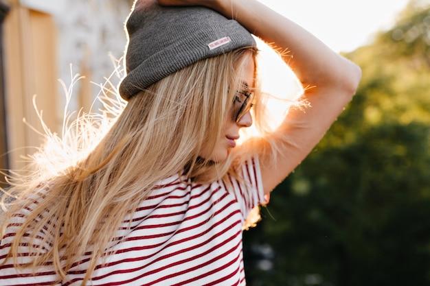 Merveilleuse femme avec petit tatouage sur le bras posant en plein air tenant un chapeau gris