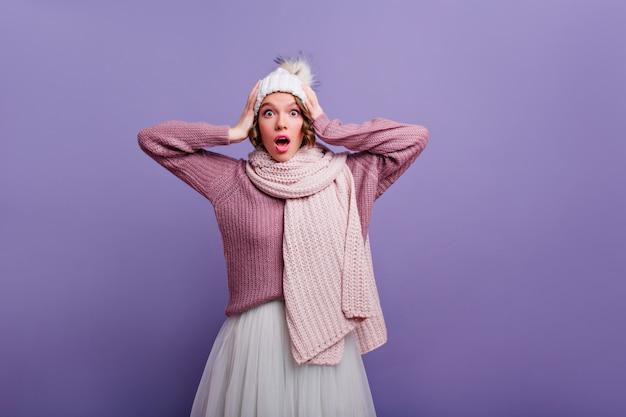 Merveilleuse femme surprise avec une écharpe tricotée touchant sa tête. portrait intérieur d'une fille caucasienne choquée en chapeau et jupe blanche.