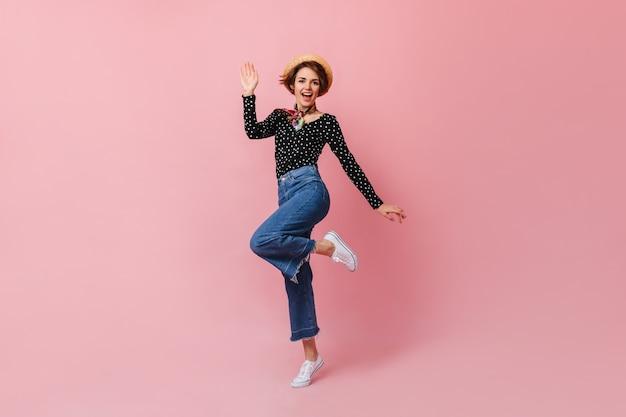 Merveilleuse jeune femme au chapeau de paille sautant sur un mur rose