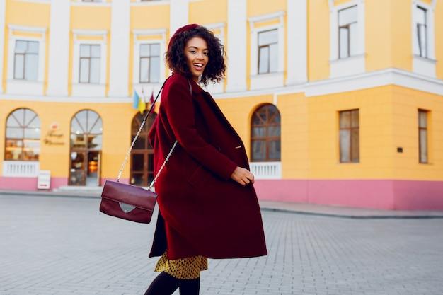 Merveilleuse jeune femme en chapeau et manteau de laine sautant