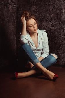 Merveilleuse jeune femme en chemise et jeans assis sur le sol au studio