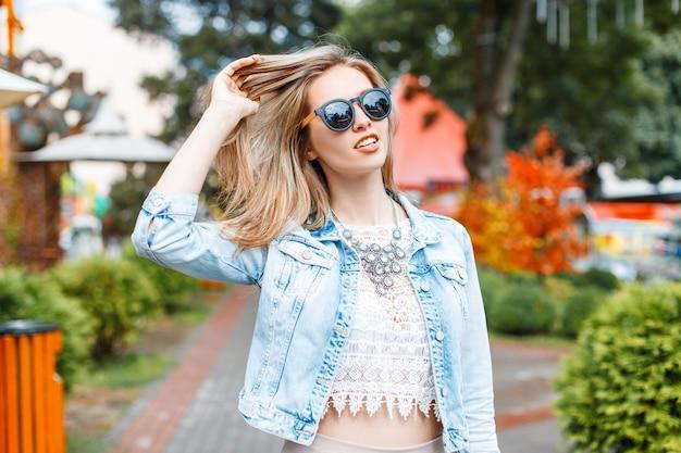 Merveilleuse jeune femme hipster dans une élégante veste en jean bleu en lunettes de soleil noires dans un chemisier en dentelle vintage avec un collier dans un parc d'attractions sur une journée de printemps ensoleillée