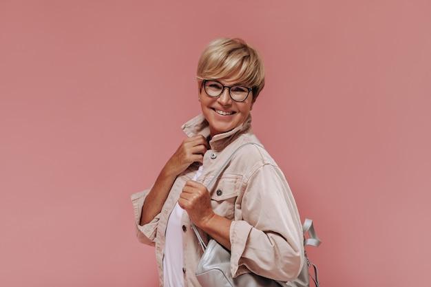 Merveilleuse vieille femme aux cheveux blonds et lunettes élégantes en veste beige et t-shirt léger souriant et posant avec sac sur fond rose.
