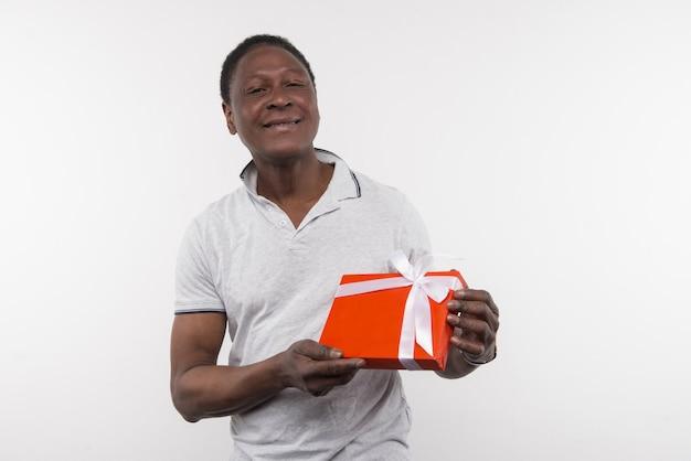 Merveilleux cadeau. joyeux homme heureux tenant la boîte essentielle tout en vous montrant le présent
