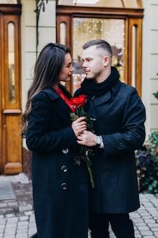 Merveilleux couple romantique avec des roses sur la rue