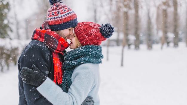 Merveilleux couple s'embrassant dans les chutes de neige
