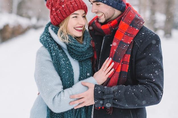 Merveilleux jeune couple dans les chutes de neige