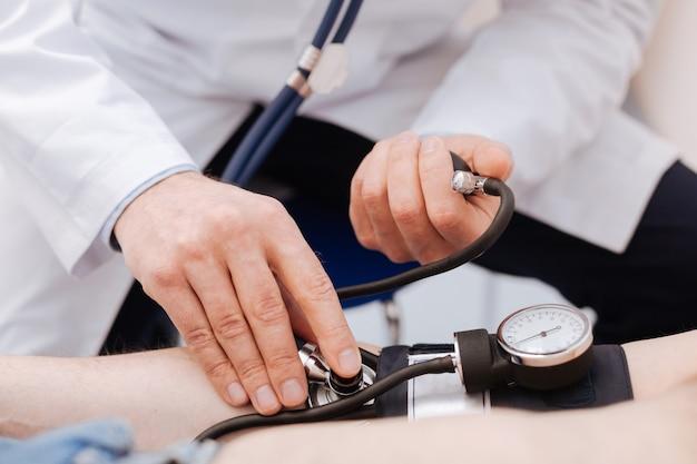 Merveilleux médecin gentil et gentil essayant de déterminer la cause des maux de tête des patients et d'exécuter des tests pour cela