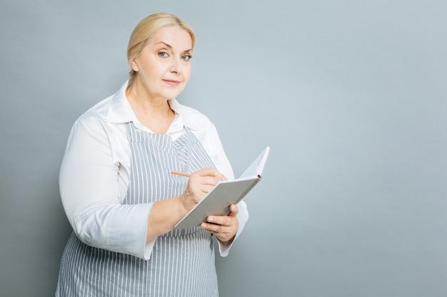 Mes notes. heureux femme tenant le cahier dans la main gauche et en appuyant sur les lèvres en se tenant debout isolé sur fond gris