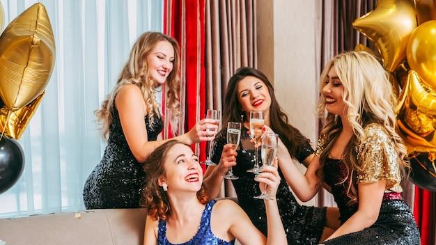 Mesdames assis autour de la fille d'anniversaire, buvant du vin mousseux pour son bonheur et son bien-être.
