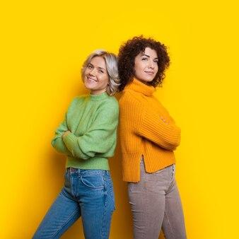 Mesdames caucasiennes aux cheveux bouclés posant dos à dos sur un mur jaune avec un espace libre avec les mains croisées