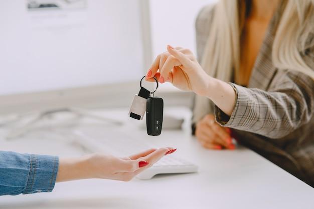 Mesdames dans un salon de voiture. femme achetant la voiture. femme élégante dans une robe bleue. le gestionnaire aide le client.