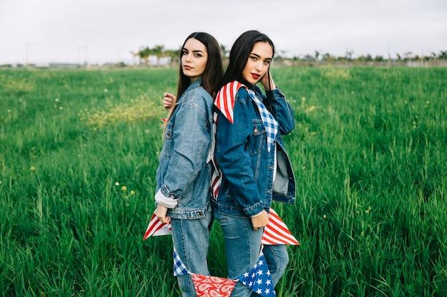 Mesdames avec des décorations américaines restant sur l'herbe verte