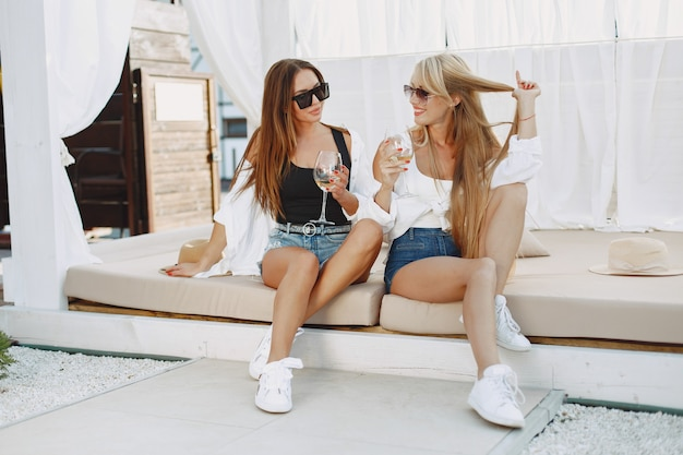 Mesdames avec de la vigne. filles en top et short. amis dans des lunettes de soleil.