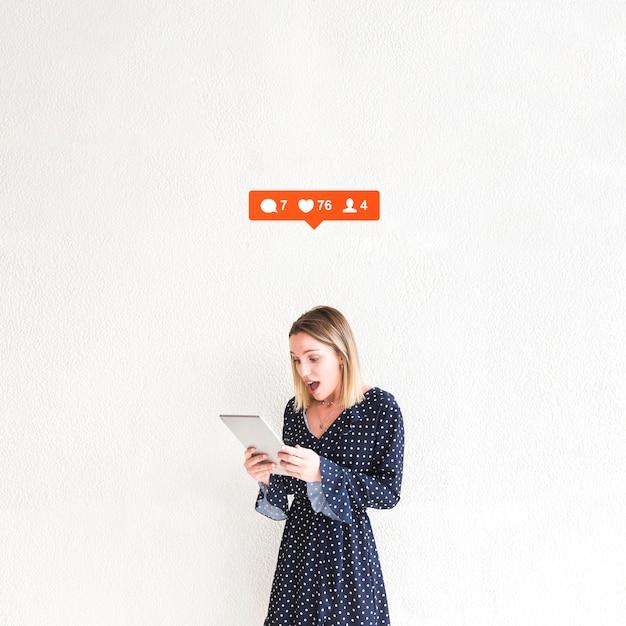Message, aimer et commenter l'option sur la femme surprise en regardant la tablette numérique