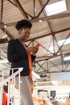 Message au téléphone. designer à la mode à la peau foncée portant des lunettes lisant un message au téléphone