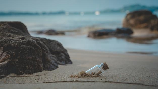 Message en bouteille sur la plage de sable