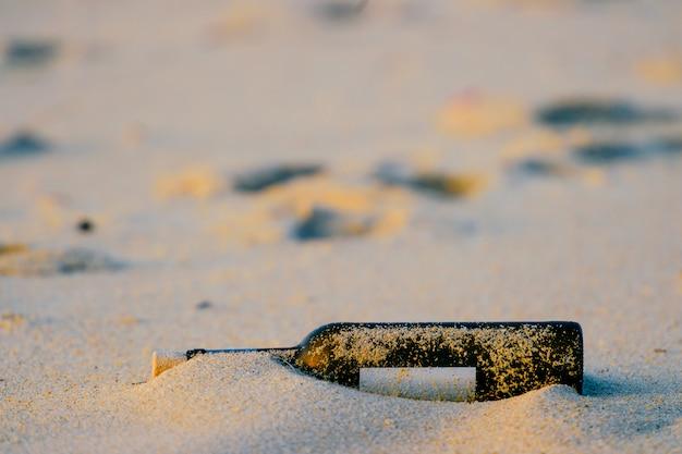 Message dans une bouteille en verre dans le sable sur la plage à l'extérieur.