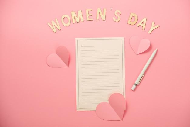 Message de la fête de la femme heureuse avec du papier coeur sur fond de papier corail
