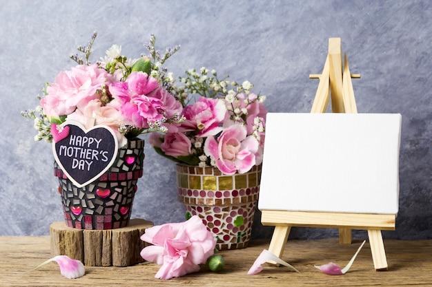 Message de fête des mères sur coeur de bois et fleurs d'oeillets roses dans un pot de fleur de mosaïque