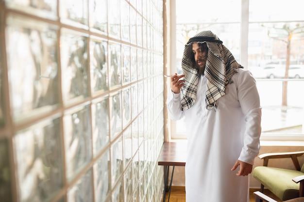 Un message. homme d'affaires arabe travaillant au bureau, centre d'affaires utilisant un appareil