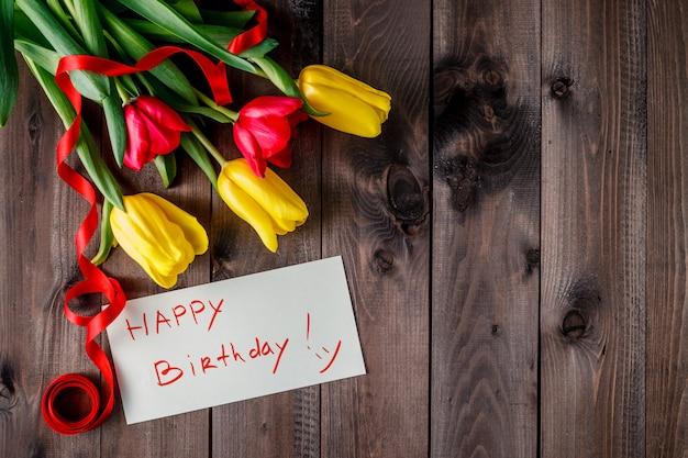 Message de joyeux anniversaire et bouquet de tulipes