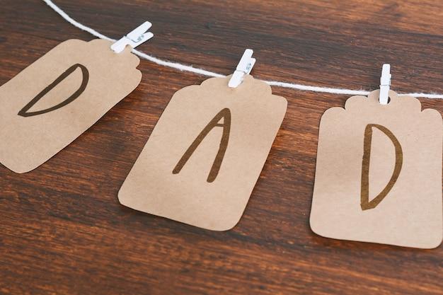 Message de papa écrit sur les étiquettes suspendus sur des pinces à linge sur fond en bois