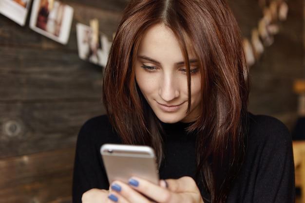 Message rapide à un ami. jolie femme européenne brune à l'aide de l'application de retouche photo sur son téléphone mobile