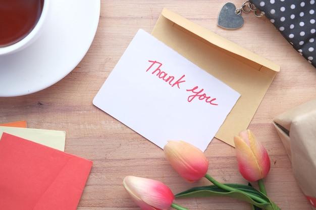 Message de remerciement et enveloppe sur table en bois