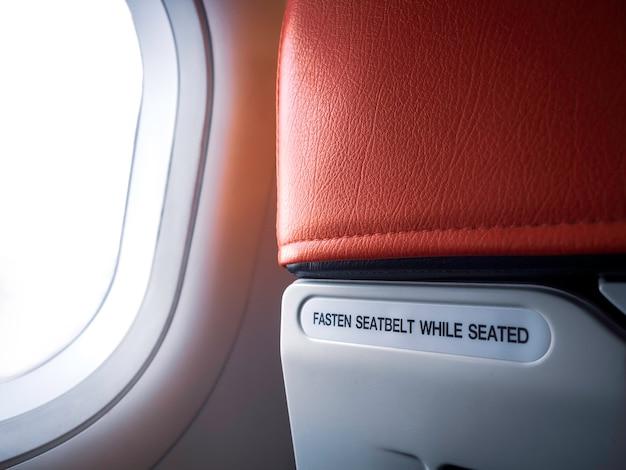 Message texte «ceinture de sécurité fixée pendant l'assise» derrière le siège rouge de l'avion près de la fenêtre