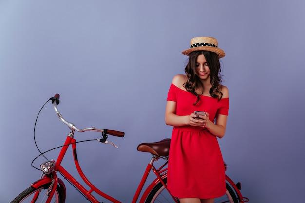 Message texto fille bouclée bien habillée sur mur violet. femme élégante caucasienne debout près de vélo et regardant l'écran du téléphone.